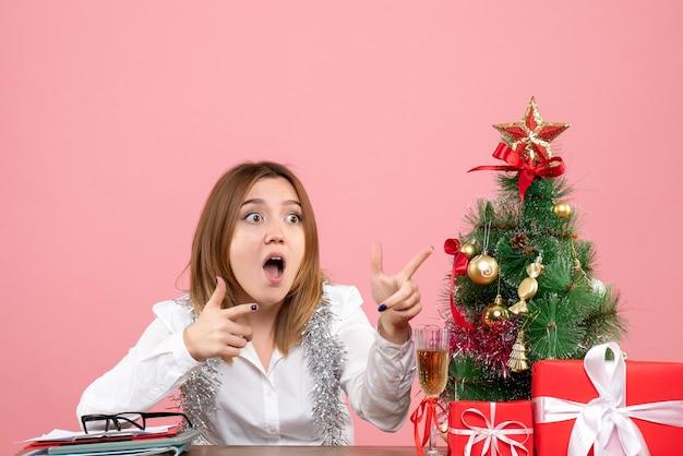 Widok z przodu pracownica siedząca wokół prezentów świątecznych na różowo
