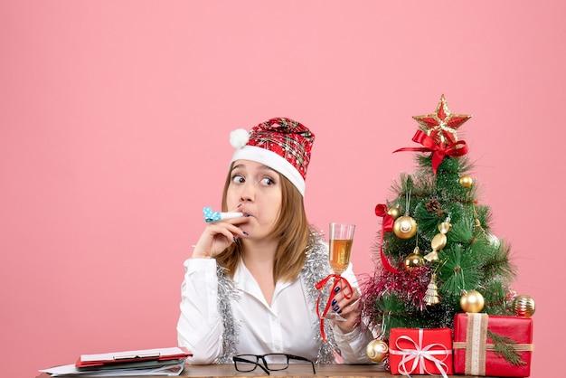 Widok z przodu pracownica trzymając kieliszek szampana na różowo