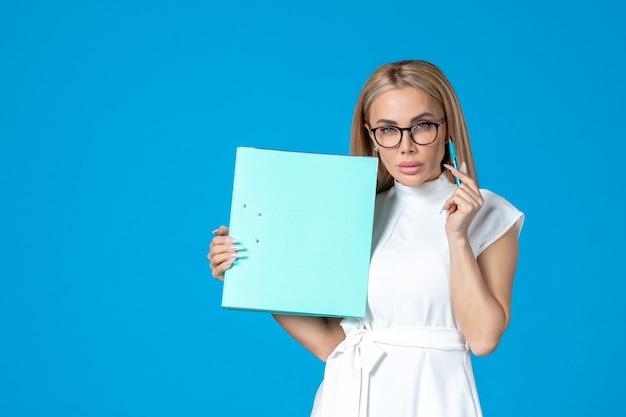 Widok z przodu pracownica w białej sukni trzymającej folder na niebieskiej ścianie
