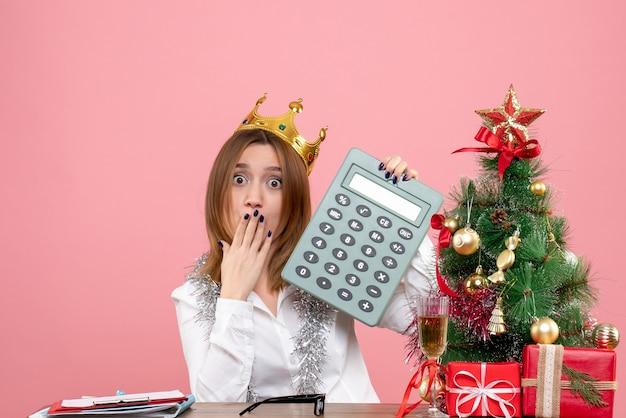 Widok z przodu pracownica w koronie trzyma kalkulator na różowo