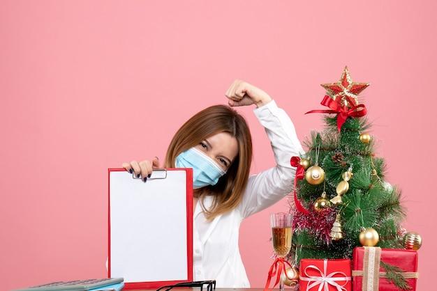 Widok z przodu pracownica w masce trzymając plik notatki na różowo