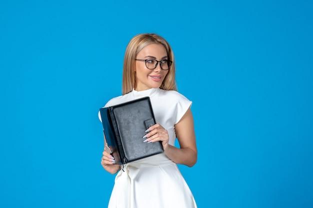 Widok z przodu pracownica w pięknej białej sukni z notatnikiem na niebieskiej ścianie