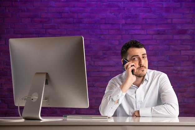 Widok z przodu pracownik biurowy płci męskiej siedzący za jego miejsce pracy mówić