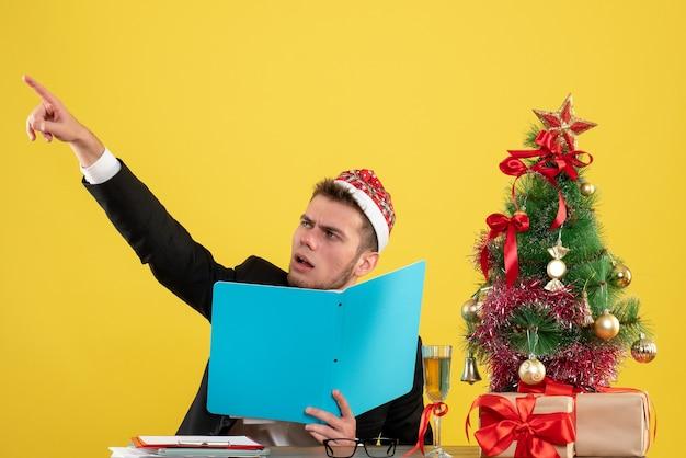 Widok z przodu pracownik płci męskiej siedzi i trzyma dokumenty na żółto