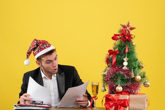 Widok z przodu pracownik płci męskiej siedzi za swoim miejscem pracy, czytanie dokumentów na żółto