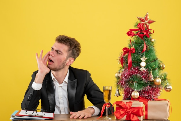 Widok z przodu pracownik płci męskiej siedzi za swoim miejscem pracy wzywając na żółto