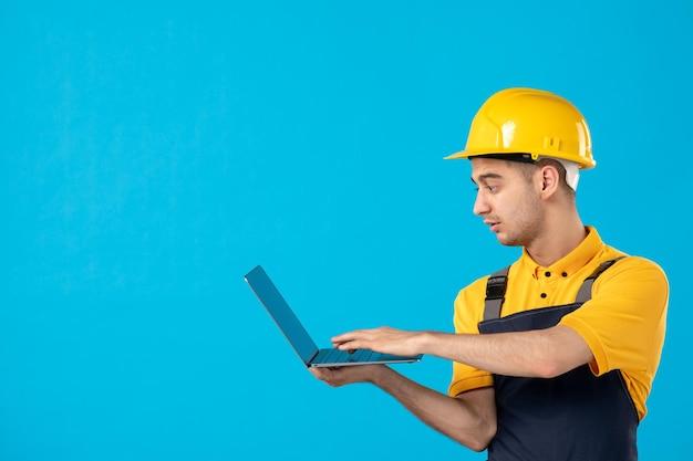 Widok z przodu pracownika płci męskiej w mundurze pracy z laptopem na niebiesko