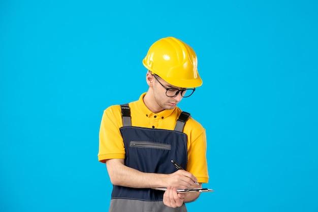 Widok z przodu pracownika płci męskiej w żółtym mundurze pisania notatek na niebiesko