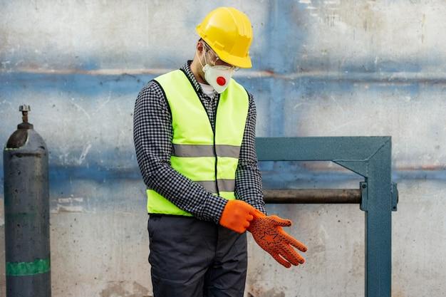 Widok z przodu pracownika w kasku zakładającym rękawice ochronne