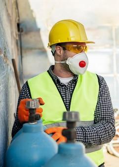 Widok z przodu pracownika z maską ochronną i kaskiem
