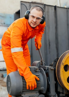 Widok z przodu pracownika ze słuchawkami i okularami ochronnymi
