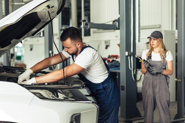 Widok z przodu pracujących pracowników serwisu samochodowego