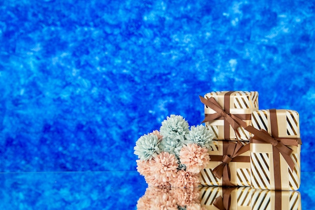 Widok z przodu prezenty świąteczne kwiaty odbite w lustrze na niebieskim niewyraźnym tle