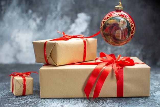 Widok z przodu prezenty świąteczne wiązane czerwonymi kokardkami na jasno-ciemnym nowym roku zdjęcie świąteczny kolorowy prezent świąteczny