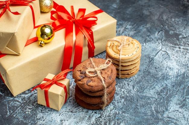 Widok z przodu prezenty świąteczne ze słodkimi ciasteczkami na jasno-ciemnym świątecznym prezentie fotograficznym świąteczny kolor nowy rok