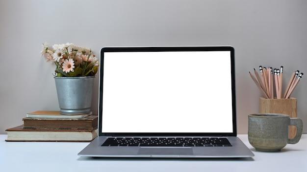 Widok z przodu prostego obszaru roboczego z białym pustym ekranem monitora komputera przenośnego i sprzętu na białym biurku.