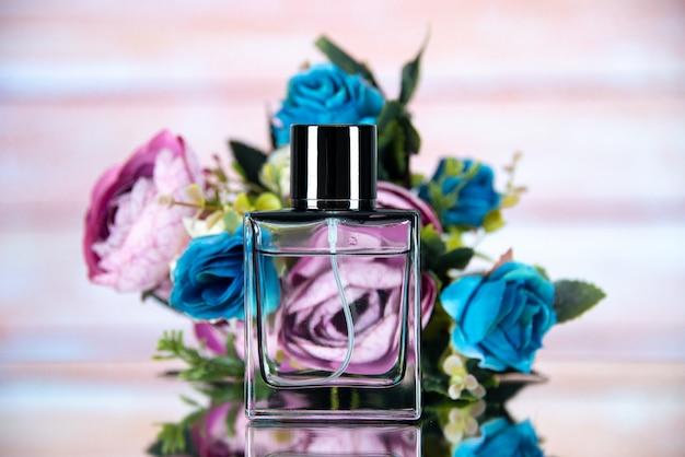 Widok z przodu prostokątnej butelki perfum w kolorze kwiatów na beżowym rozmytym