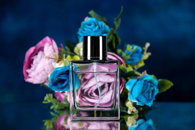 Widok z przodu prostokątnej butelki perfum w kolorze kwiatów na ciemnoniebieskim