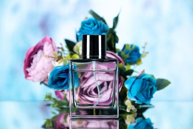Widok z przodu prostokątnej butelki perfum w kolorze kwiatów na jasnoniebieskim kolorze