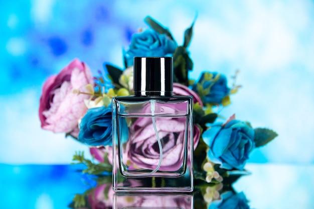 Widok z przodu prostokątnej butelki perfum w kolorze kwiatów na jasnoniebieskim rozmytym