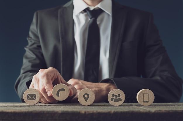 Widok z przodu przedstawiciela obsługi klienta biznesowego umieszczającego pięć drewnianych kółek z ikonami kontaktów i informacji w rzędzie.