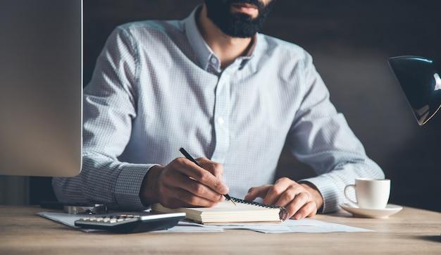 Widok z przodu przemyślanych wykonawczych mężczyzn rasy kaukaskiej pracujących na komputerze przy biurku w nowoczesnym biurze