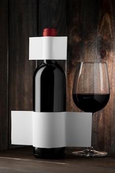 Widok z przodu przezroczystej butelki wina i szkła z pustą etykietą