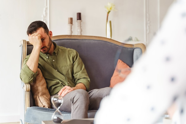 Widok z przodu przygnębionego młodego mężczyzny siedzącego z głową opartą na pięści