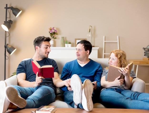 Widok z przodu przyjaciół na kanapie z książkami