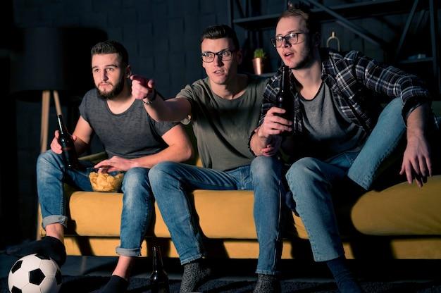 Widok z przodu przyjaciół płci męskiej, którzy razem oglądają sport w telewizji, jedząc przekąski i piwo