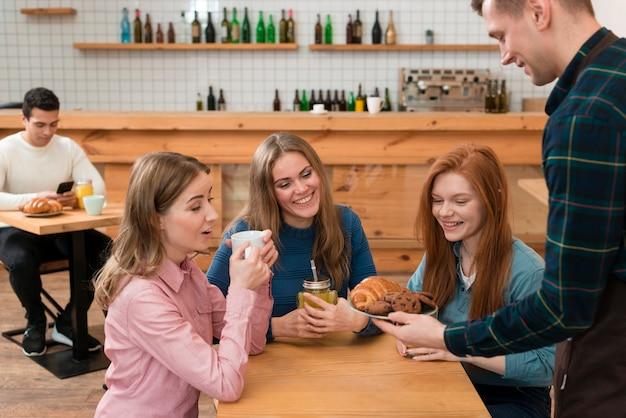 Widok z przodu przyjaciół siedząc przy stole