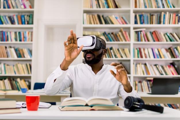 Widok z przodu przystojnego, czarnoskórego, brodatego młodego chłopca w zestawie rozszerzonej rzeczywistości, siedzącego przy biurku w bibliotece i poruszającego rękami na wirtualnym ekranie lub książce