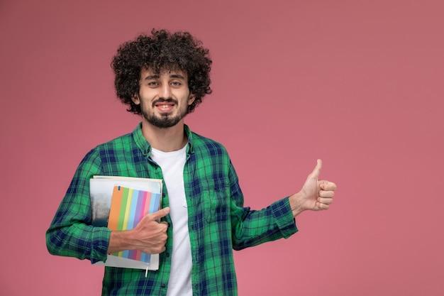 Widok z przodu przystojny facet dając kciuki i trzymając zeszyty