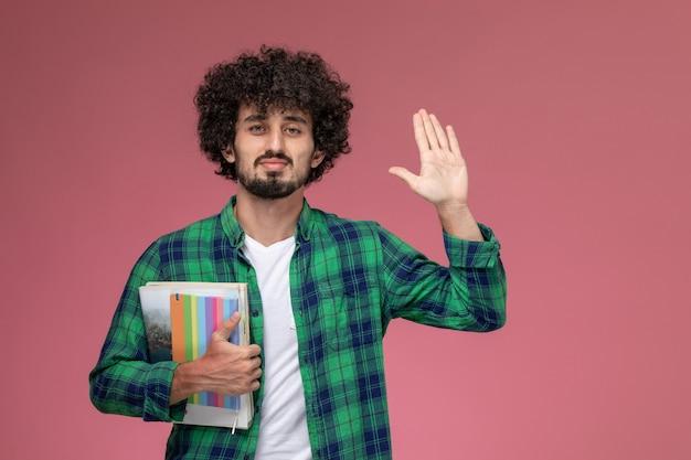 Widok z przodu przystojny facet dając piątkę z notebookami