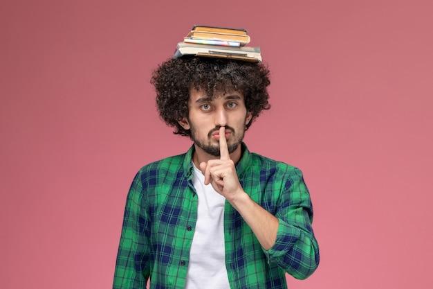 Widok z przodu przystojny facet kładąc jej zeszyty, pokazując gest ciszy