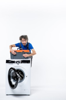 Widok z przodu przystojny mechanik zamykający torbę na narzędzia za pralką na białej przestrzeni