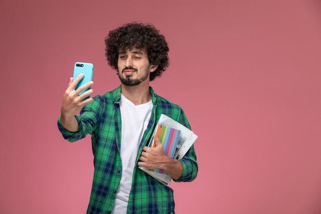 Widok z przodu przystojny mężczyzna biorąc proste selfie ze swoimi notebookami