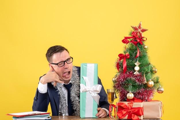 Widok z przodu przystojny mężczyzna dzwoniący do mnie znak telefonu siedzi przy stole w pobliżu choinki i przedstawia na żółto