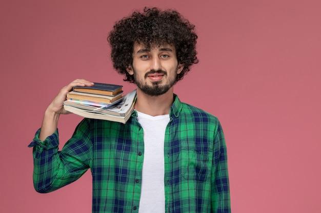 Widok z przodu przystojny mężczyzna kładąc swoje zeszyty na ramionach