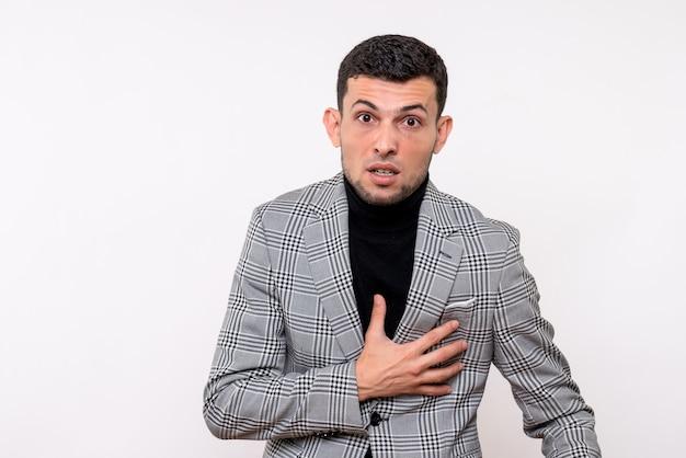 Widok z przodu przystojny mężczyzna w garniturze, trzymając jego klatkę piersiową, stojąc na białym tle