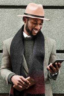 Widok z przodu przystojny mężczyzna w szarej kurtce, patrząc na jego telefon