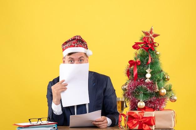 Widok z przodu przystojny mężczyzna z santa hat trzyma dokumenty siedząc przy stole w pobliżu choinki i przedstawia na żółto