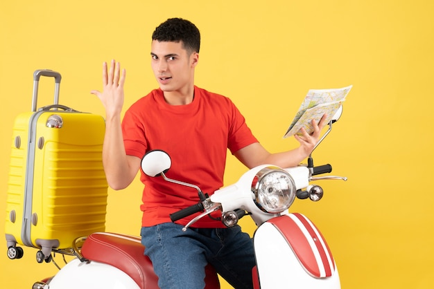 Widok z przodu przystojny młody człowiek na motorowerze z walizką trzymając mapę