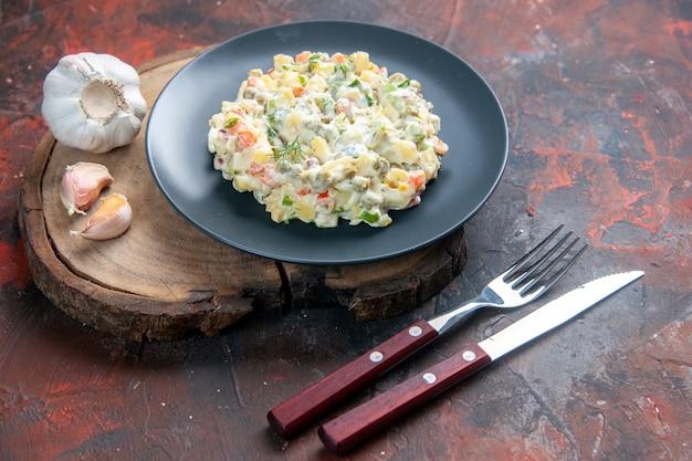 Widok z przodu pyszna rosyjska sałatka ze sztućcami na ciemnym tle chleb jedzenie danie posiłek kolacja pozioma obiad restauracja