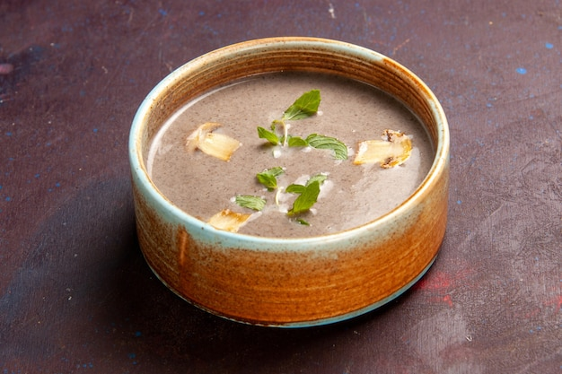 Widok z przodu pyszna zupa grzybowa wewnątrz talerza w ciemnej przestrzeni
