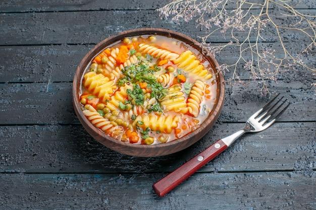Widok z przodu pyszna zupa makaronowa ze spiralnego włoskiego makaronu z zielenią na ciemnym rustykalnym daniu obiadowym na biurku włoski sos do zupy makaronowej