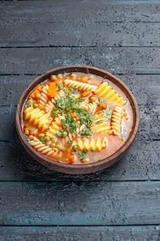 Widok z przodu pyszna zupa makaronowa ze spiralnego włoskiego makaronu z zieleniną na ciemnym daniu na biurko włoska zupa makaronowa sos obiadowy