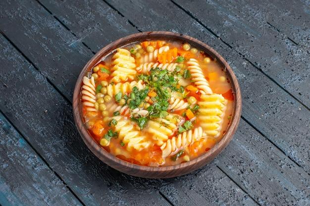 Widok z przodu pyszna zupa makaronowa ze spiralnego włoskiego makaronu z zieleniną na ciemnym daniu na biurko włoski makaron obiadowy sos zupa