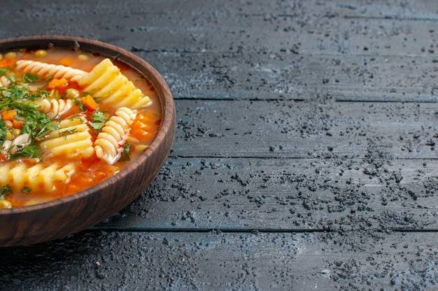 Widok z przodu pyszna zupa makaronowa ze spiralnego włoskiego makaronu z zieleniną na ciemnym daniu na biurko włoski sos makaronowy kolacja zupa
