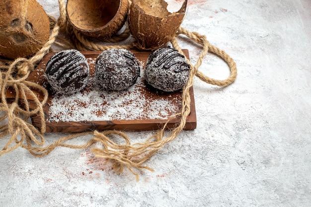 Widok z przodu pyszne ciasta czekoladowe z kokosem na białej powierzchni biszkoptowe ciasto cukrowe słodka herbata cookie